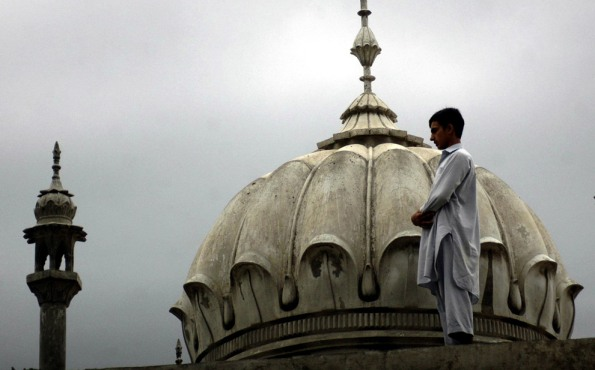 A Fasting Muslim Boy Performing Nafil Namaz,  from Roof Top of a Mosque  in India.