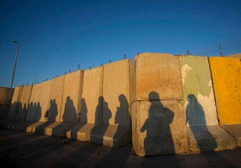 Shadows of Palestinian women are seen at Qalandiya checkpoint outside the West Bank city of Ramallah August 28, 2009, as they try to reach the Al-Aqsa Mosque in Jerusalem on the first Friday of the Muslim holy month of Ramadan. (Reuters, Fadi Arouri)